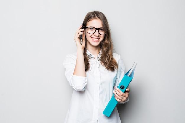 La ragazza con gli occhiali si è vestita in maglietta bianca dell'ufficio rigoroso sta davanti al muro bianco e tiene il suo telefono e la cartella nelle mani