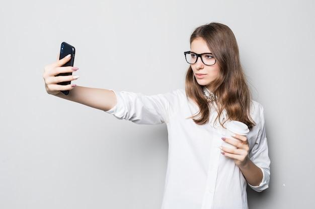 La ragazza con gli occhiali si è vestita in maglietta bianca dell'ufficio rigoroso sta davanti al muro bianco e tiene il suo telefono nelle mani