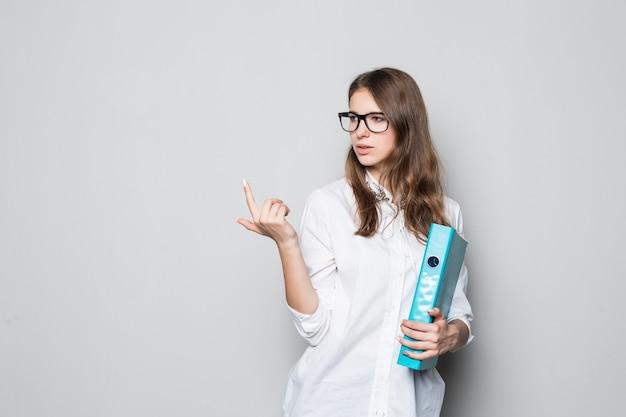 Giovane ragazza con gli occhiali vestita in t-shirt bianca da ufficio rigoroso si trova di fronte al muro bianco con la cartella blu per i documenti nelle sue mani