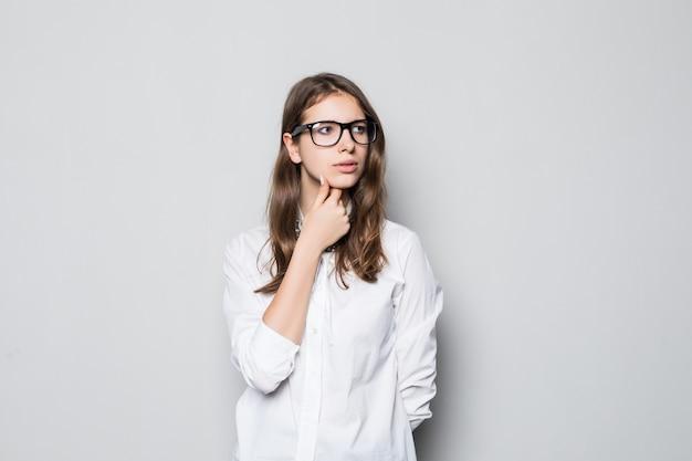Giovane ragazza con gli occhiali vestita in t-shirt bianca ufficio rigoroso si trova davanti al muro bianco