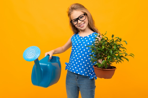 Young girl in glasses holds a leaf plant in her hands and a watering can on an orange
