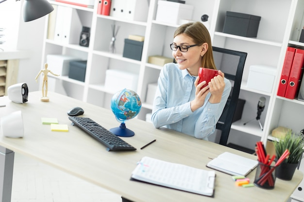 A young girl in glasses is sitting at a table, holding a red cup in her hands and looking at the globe.