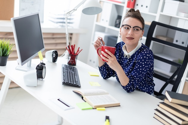 A young girl in glasses sits in the office at the table, holds a pencil and a red cup in her hands.