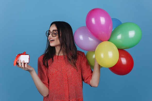 Young girl in glasses stands with a little present and balloons