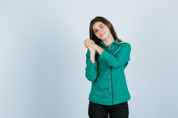 Giovane ragazza in camicetta verde, pantaloni neri stringendo le mani sul petto e guardando allegra, vista frontale.