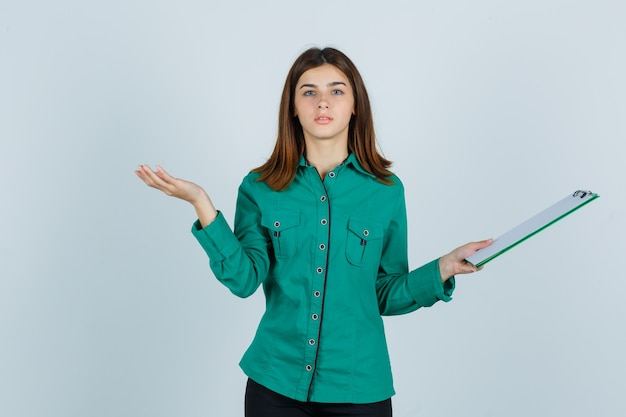 Young girl in green blouse, black pants holding clipboard, spreading palm aside and looking serious , front view.