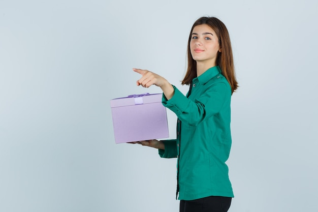Young girl in green blouse, black pants holding gift box, pointing away with index finger and looking cheery , front view.