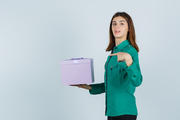 Young girl in green blouse, black pants holding gift box, pointing at it and looking cheery , front view.