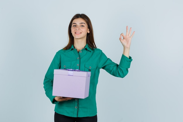 Young girl in green blouse, black pants holding gift box, showing ok sign and looking merry , front view.