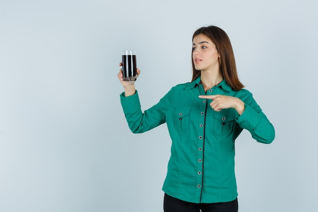 Young girl in green blouse, black pants holding glass of black liquid, pointing at it and looking focused , front view.