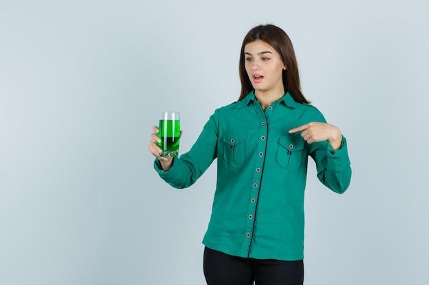 Giovane ragazza in camicetta verde, pantaloni neri con in mano un bicchiere di liquido verde, indicandolo con il dito indice e guardando scioccato, vista frontale.