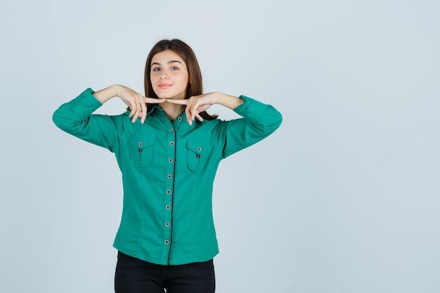 Giovane ragazza in camicetta verde, pantaloni neri tenendo le dita indice sotto il mento e guardando carino, vista frontale.