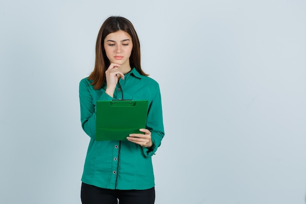 Young girl in green blouse, black pants looking at clipboard, propping chin and looking focused , front view.