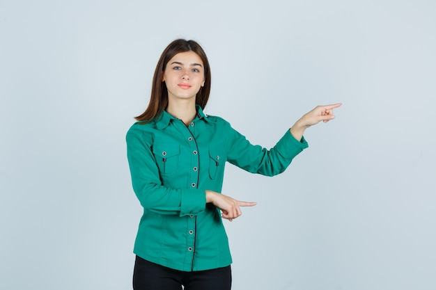 Young girl in green blouse, black pants pointing right with index fingers and looking happy , front view.