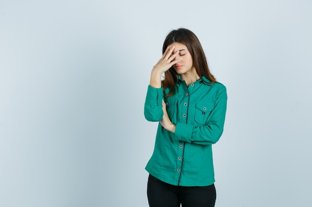 Young girl in green blouse, black pants putting hand on forehead and looking exhausted , front view.