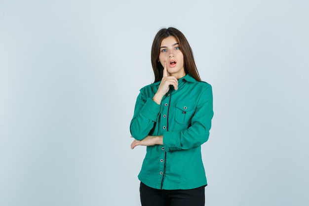 Young girl in green blouse, black pants putting index finger near mouth, keeping mouth wide open and looking surprised , front view.