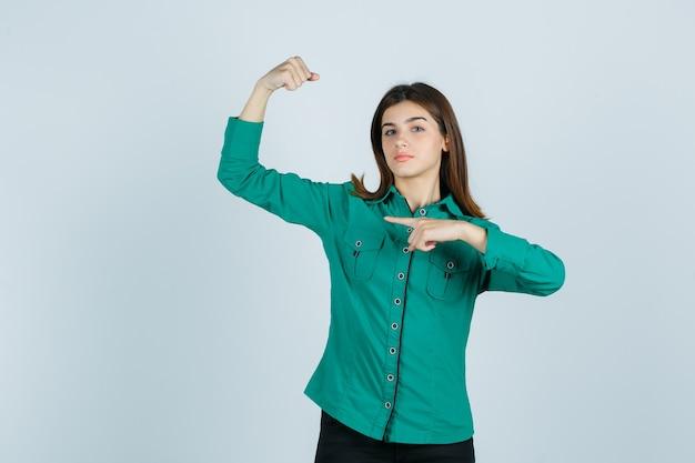 Giovane ragazza in camicetta verde, pantaloni neri che mostra i muscoli del braccio, indicandolo e guardando fiducioso, vista frontale.