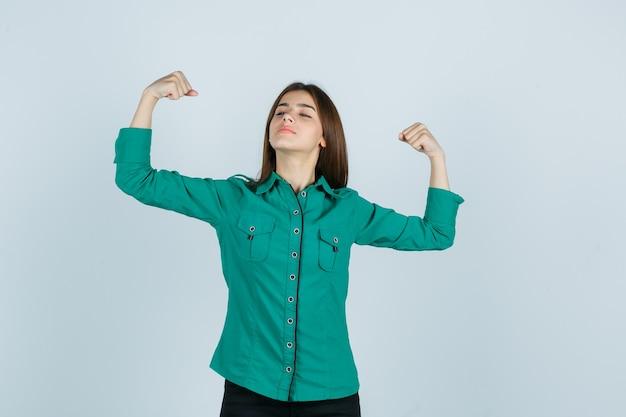 Giovane ragazza in camicetta verde, pantaloni neri che mostra il gesto del vincitore e sembra fortunato, vista frontale.