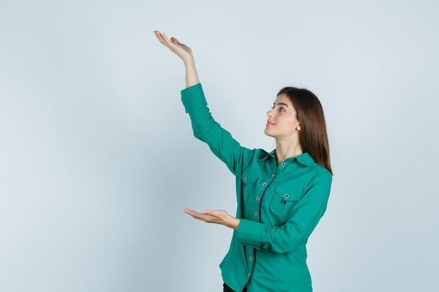 Giovane ragazza in camicetta verde, pantaloni neri che allungano le mani come tenendo qualcosa e guardando allegro, vista frontale.