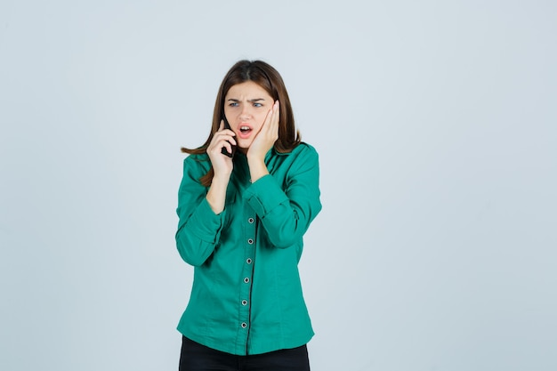 Giovane ragazza in camicetta verde, pantaloni neri, parlando al telefono, tenendo la mano sulla guancia e guardando scioccato, vista frontale.