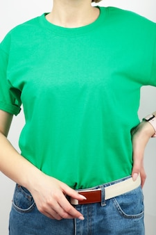 Young girl in green t-shirt on a grey surface