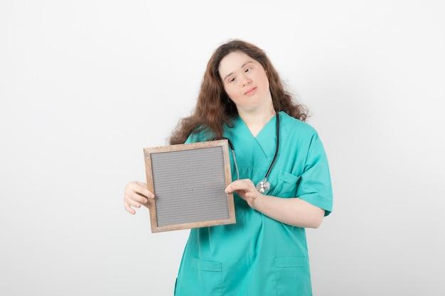 Giovane ragazza in uniforme verde che tiene una cornice.