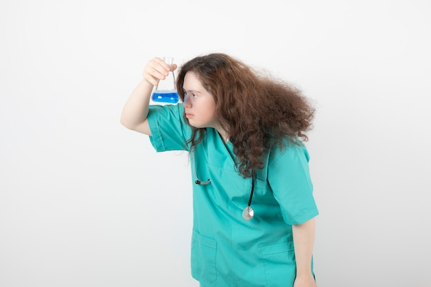 Young girl in green uniform holding a glass jar with blue liquid.