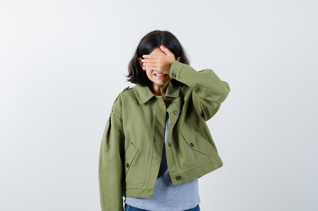 Young girl in grey sweater, khaki jacket, jean pant covering eyes with hand and looking cute , front view.