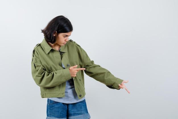 Giovane ragazza in maglione grigio, giacca color kaki, pantaloni jeans rivolti verso il basso e verso destra con le dita indice e guardando focalizzato, vista frontale.