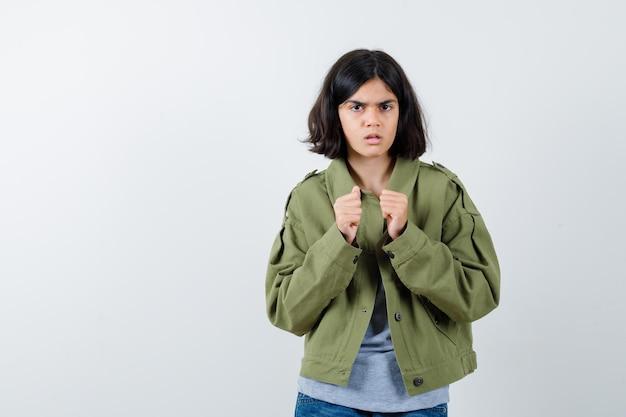 Giovane ragazza in maglione grigio, giacca color kaki, pantaloni di jeans in piedi in posa da pugile e dall'aspetto serio, vista frontale.