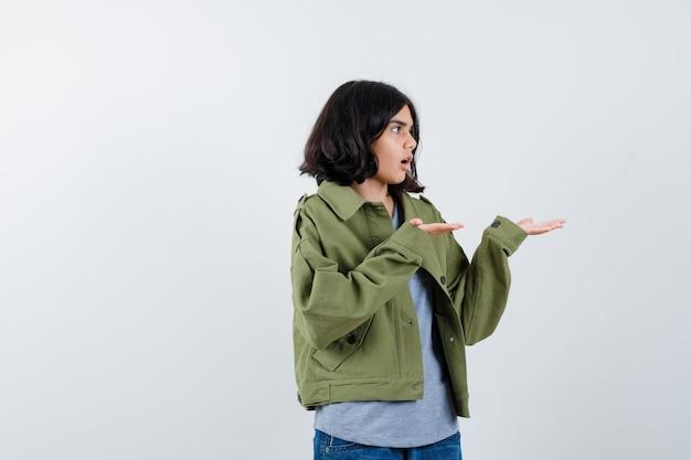 Giovane ragazza in maglione grigio, giacca kaki, pantaloni di jeans che allungano le mani come tenendo qualcosa di immaginario e guardando sorpreso, vista frontale.
