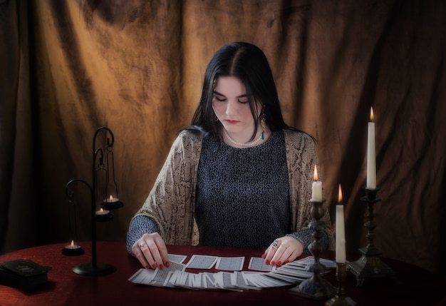 Young girl guessing with tarot cards on brown surface