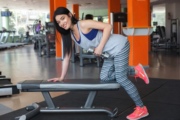 Young girl in the gym working out with dumbbells