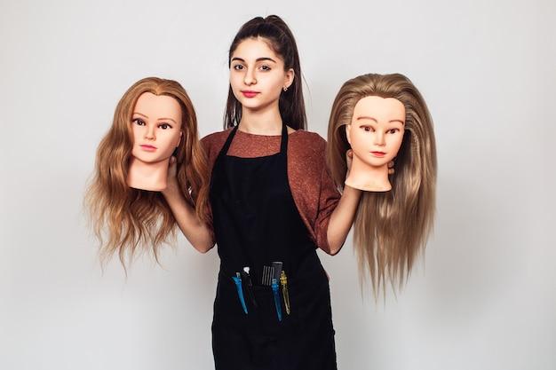 若い女の子の美容師は、2つのマネキンの頭を手に持っています。