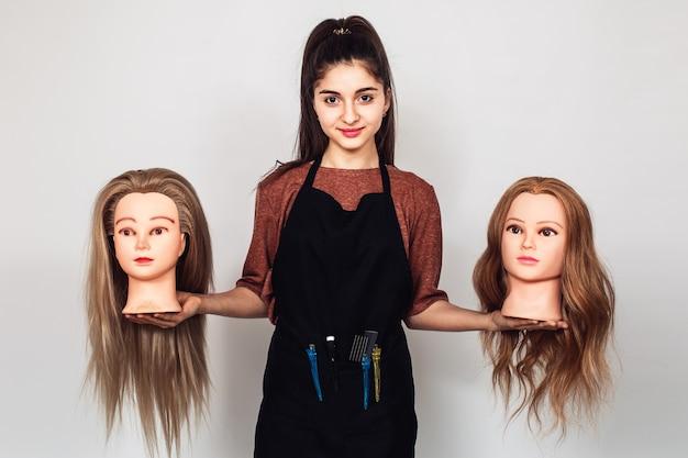 Парикмахер молодой девушки держит в руках две головы манекена.