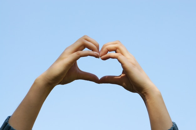 Young girl hands holding hands in heart shape with the clear blue sky background