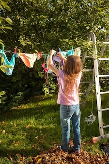 Young girl hanging clothes on clothesline at garden