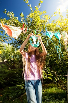Young girl hanging clothes with clothespins at sunny day