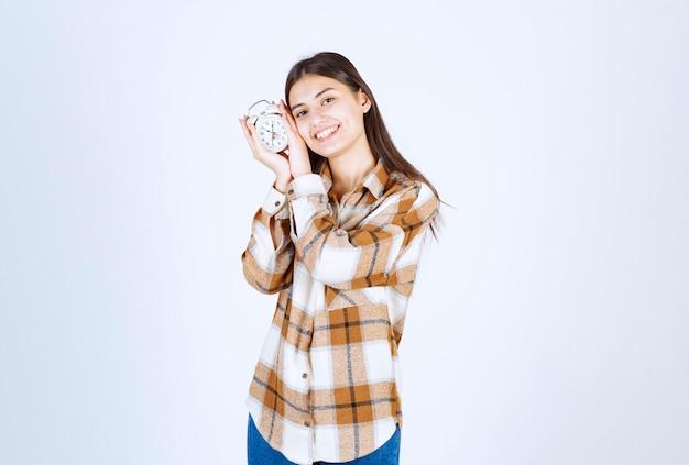 Молодая девушка счастливо обнимает будильник на белой стене.