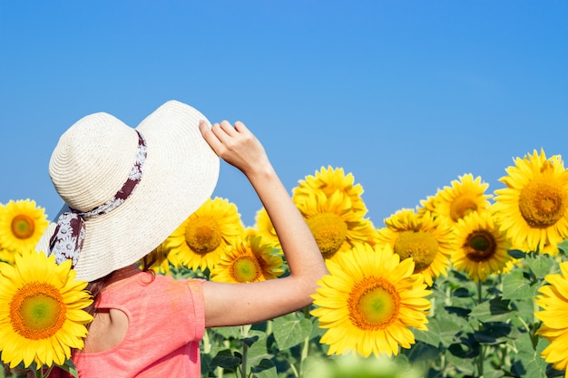 Young girl in a hat in a field of sunflowers in the summer.