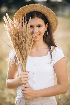 Young girl in a hat in a field of wheat