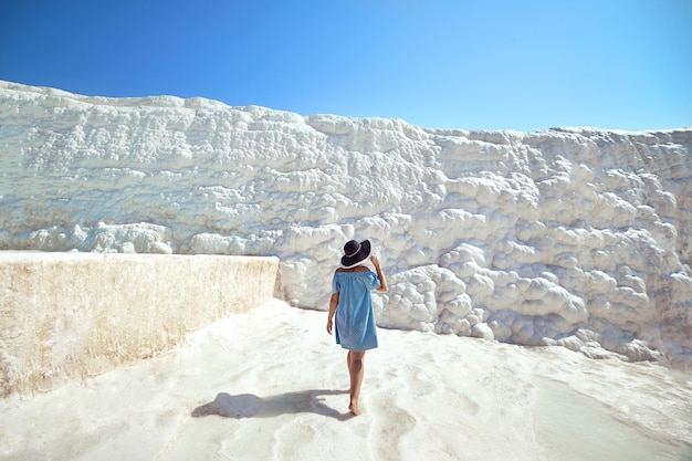 Young girl in hat looking on travertine pools and terraces in pamukkale. cotton castle in southwestern turkey
