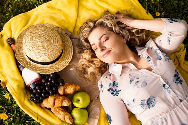Young girl in hat lying on the plaid with wine and fresh food. picnic. natural light
