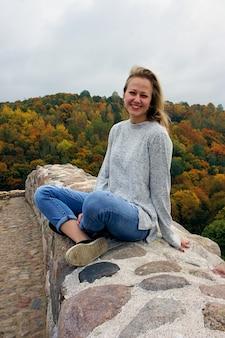 Молодая девушка гуляет в осеннем лесу. красивый парк с сухими желтыми и красными листьями и разноцветными деревьями.