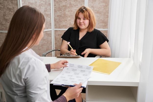 彼女のオフィスで医者との約束を持っている若い女の子