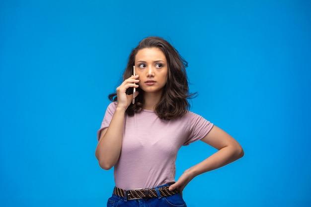 Молодая девушка звонит на свой смартфон и выглядит серьезно.