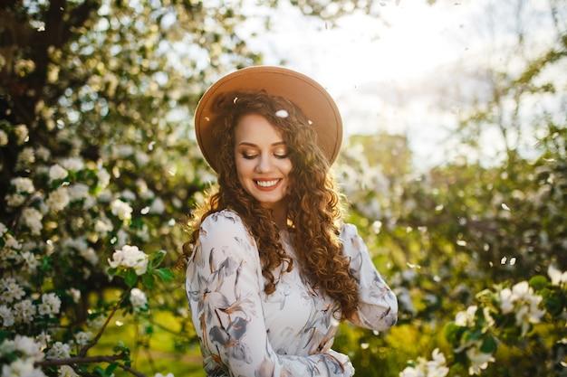 明るい春の日に咲く木々の間で楽しんでいる少女。ベージュの帽子と白いドレスを着た女性は、庭の木の花の花のにおいがします。