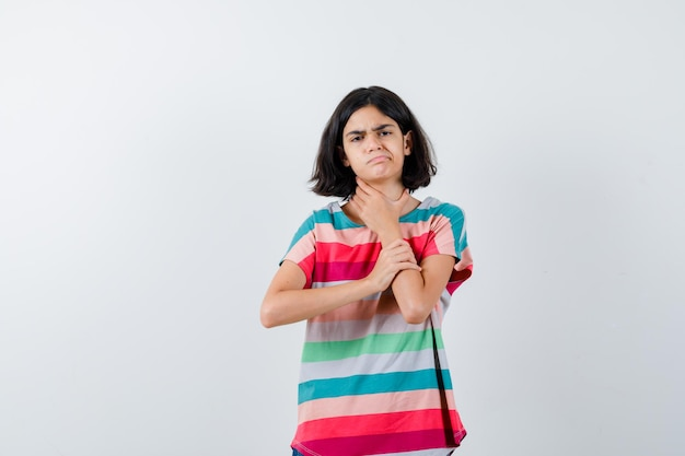 Giovane ragazza che ha dolore al collo in maglietta a righe colorate e sembra esausta, vista frontale.