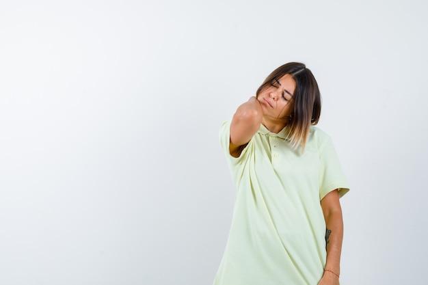 Молодая девушка с болью в шее в футболке выглядит измученной. передний план.