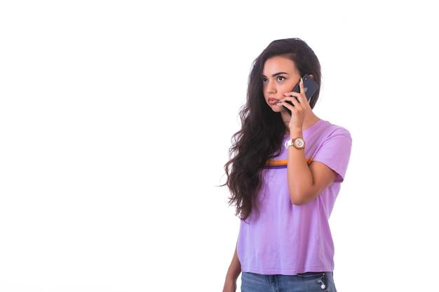 Ragazza giovane avente una telefonata e parlando con uno smartphone nero